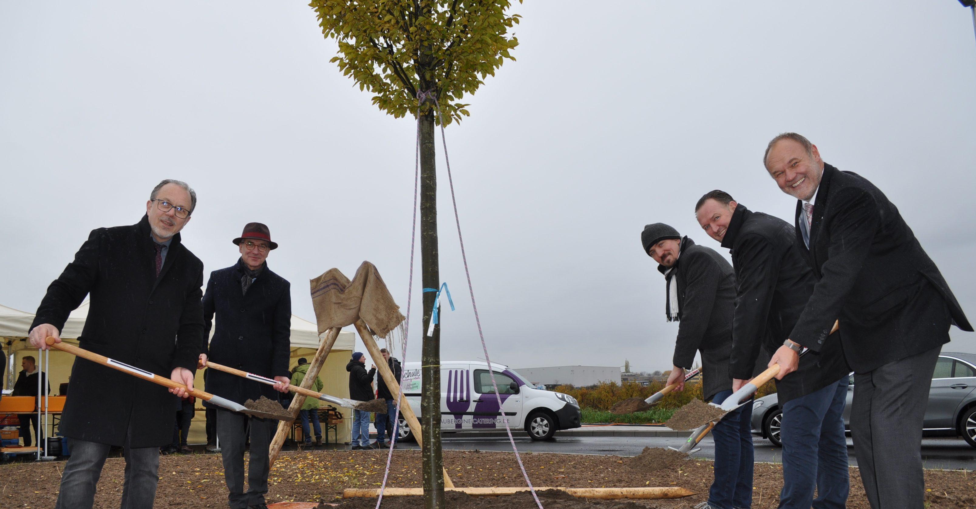 Foto zeigt Vertreter der Stadt u.a. beim Pflanzen ines Baums